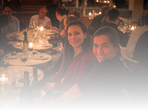 Two young women smiling at a dinner party, Paris.